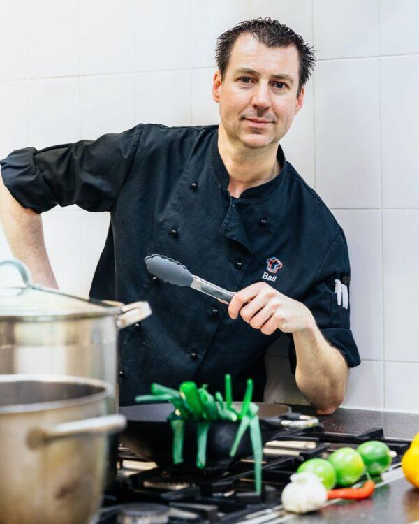 Kok staat met een lepel in zijn hand achter het fornuis met pannen